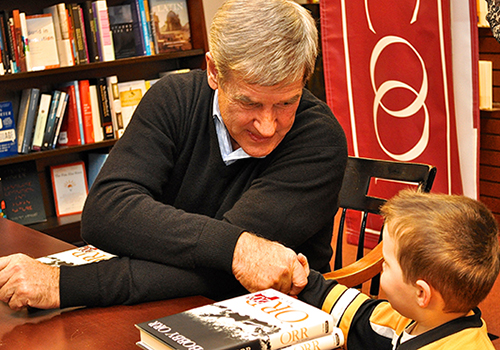 Hockey great Bobby Orr shakes hands with one of his littlest fans at a recent book signing at The Harvard COOP bookstore in Cambridge, Massachusetts.