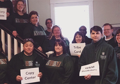 William & Mary staff members model the Charter Day t-shirt, including William & Mary Bookstore Manager, Cathy Pacheco (on stairs, 2nd from left).