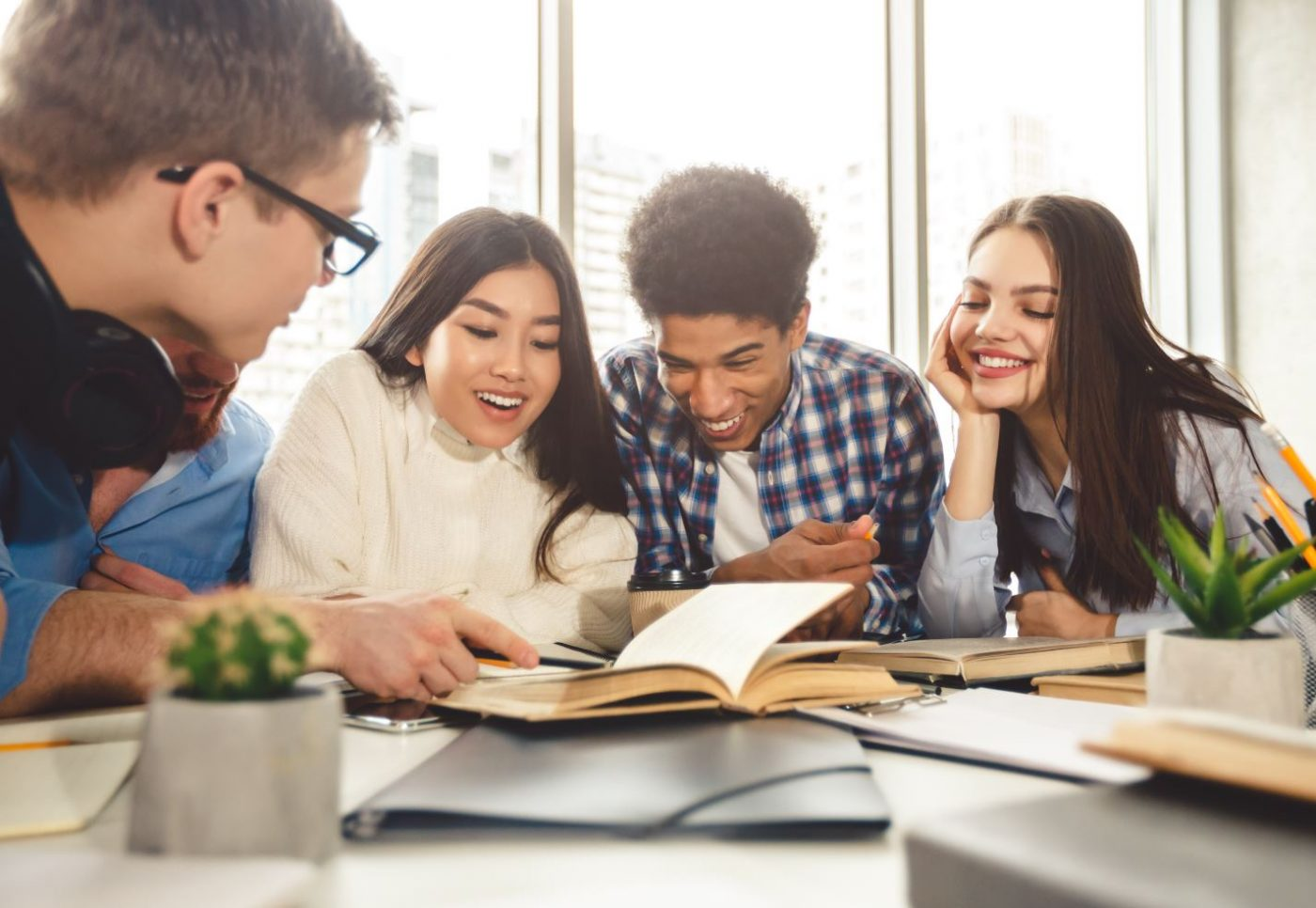 4 students reviewing textbooks scattered across a table
